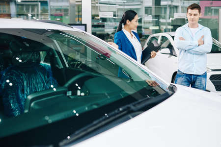 Asian female car dealership manager offering customer to test drive a car before buying it