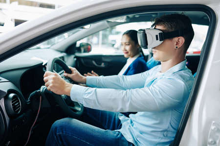 Young man in virtual reality headset test driving new car in dealership, manager sitting in passenger seat 免版税图像 - 156760240
