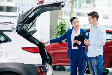 Car dealership manager opening car trunk when showing automobile to customer 免版税图像
