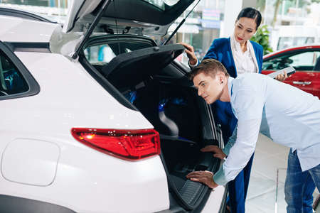 Handsome young man looking inside car trunk in dealership 免版税图像