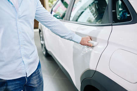 Close-up image of man opening back door of new car