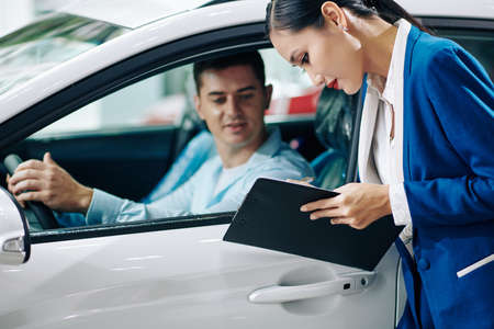 Car dealership manager filling customer details in document before test drive 免版税图像 - 156760247