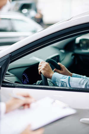 Man sitting in new car in dealership with hands on steering wheel 免版税图像