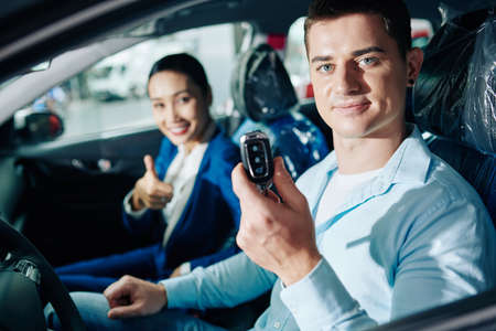 Portrait of smiling young man showing electronic keys of new car he bought in car dealership
