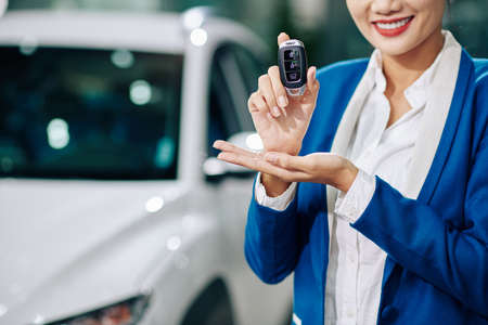 Cropped image of smiling car dealership manager showing electronic keys 免版税图像