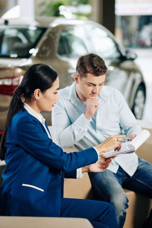 Car dealership manager asking customer to sign vehicle purchase agreement 免版税图像