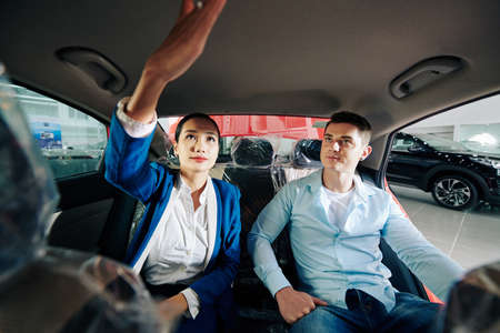 Car dealership manager showing customer how to turn on light in automobile compartment 免版税图像