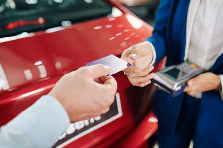 Hands of man giving credit card to manager when paying for rental car