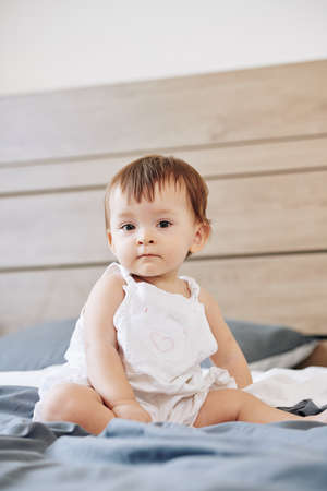 Portrait of serious little baby girl sitting on bed and looking at camera Reklamní fotografie