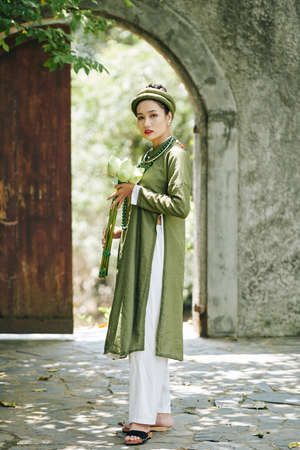 Full-length portrait of young pretty woman in traditional Vietnamese costume holding bouquet of lotus flowers