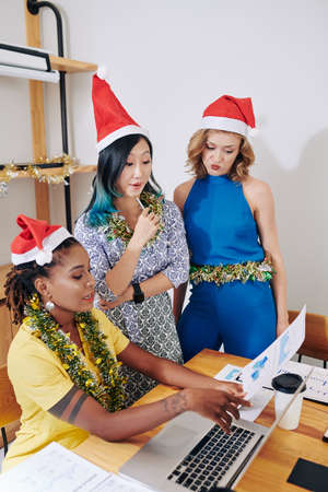 Multi-ethnic group of young businesswomen in Santa Claus hats discussing poor figures in financial reports