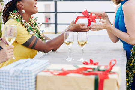 Cropped image of happy women exchanging presents and drinking champagne at Christmas party