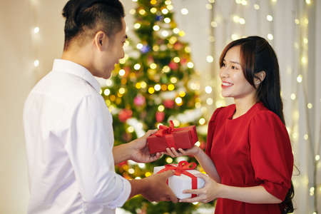 Beautiful smiling young Vietnamese couple exchanging Christmas presents at home Stock Photo
