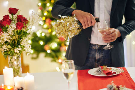 Cropped image of young man pouring glass of champagne at Christmas party