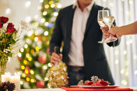 Cropped image of couple clinking champagne glasses at Christmas party