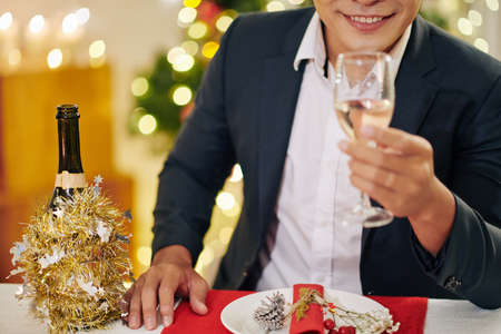 Cropped image of smiling Christmas party guest drinking glass of champagne