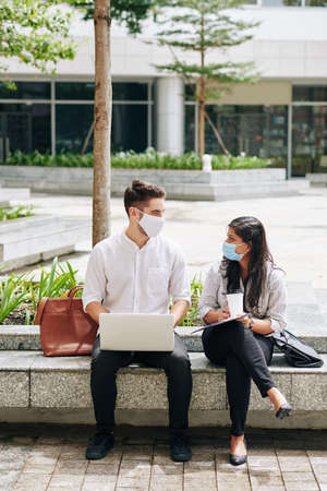 Multi-ethnic unversity students in medical masks spending time on campus and working on project