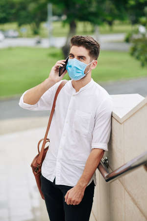 Portrait of handsome young man in medical mask standing outdoors and talking on phone