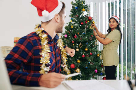 Beautiful smiling Indian businesswoman asking colleague how to decorate Christmas tree in office
