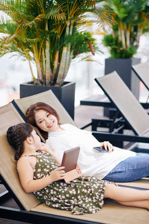 Happy Vietnamese woman lying on chaise-lounge next to her preteen daughter and touching her face with love and care