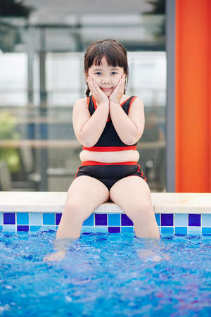 Cute Asian little girl sitting on pool edge, touching her cheeks and looking at camera 免版税图像