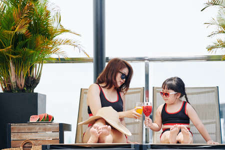 Mother and little daughter clinking glasses of fruit cocktails when relaxing on chaise-lounges