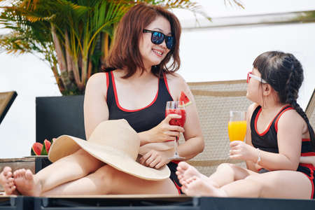 Mother and little daughter drinking delicious fruit cocktails and talking when resting by swimming pool in hotel