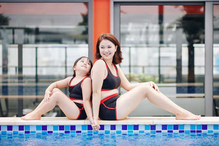 Asian mother and daughter in same swimsuits sitting on pool edge back to back, holding hands and looking at each other