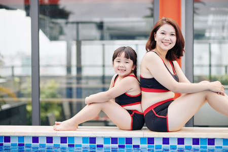 Smiling Asian mother and daughter sitting on edge of swimming pool in swimsuits and looking at camera