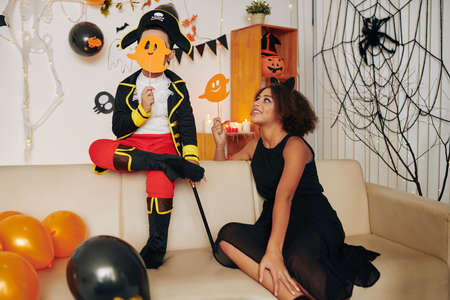 Pretty smiling girl in black dress sitting on sofa and looking at younger brother in pirate costume hiding behind paper ghost Banque d'images