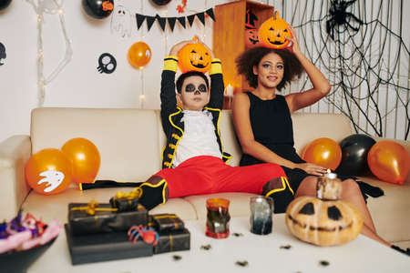 Funny brother and sister with Halloween make-up sitting on sofa in decorated room and posing with Jack-o-lanterns on their heads