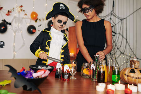 Brother and sister in spooky costumes making Halloween treats for house party Banque d'images