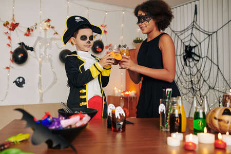 Children clinking decorated glasses with sweet drinks at Halloween party Banque d'images