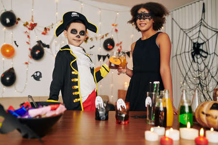 Cheerful brother and sister celebrating Halloween at home, wearing spooky costumers and drinking sweet cocktails Banque d'images