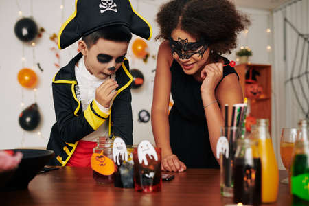 Excited children choosing what drink to try at Halloween party Banque d'images