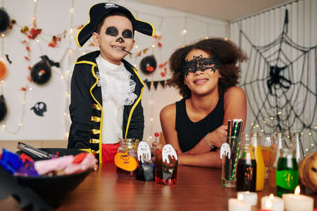 Portrait of happy excited brother and sister in Halloween costumes standing at table with party snacks and drinks