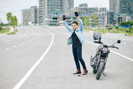 Motorcyclist raising hands and trying to attract attention of drivers when standing on road next to his broken motorcycle