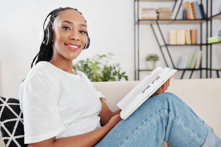Black young smiling woman in headphones sitting on sofa and reading language students book Archivio Fotografico
