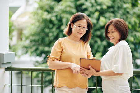 Senior Vietnamese women discussing photos on screen of digital tablet