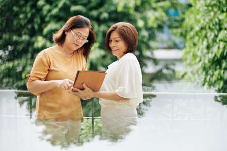 Smiling senior Vietnamese woman showing new application on tablet computer to female friend