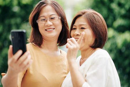 Asian senior women video calling their friend when standing outdoors