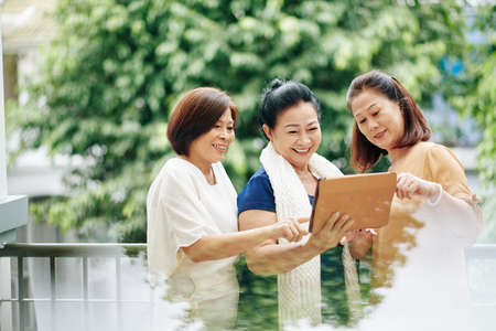 Cheerful senior Vietnamese female friends using new application on tablet computer, discussing photos or news