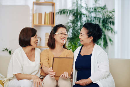 Group of happy Vietnamese elderly women watching funny videos or looking at photos on tablet computer when meeting at home