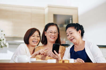 Group of cheerful Vietnamese senior women watching funny videos on smartphone screen