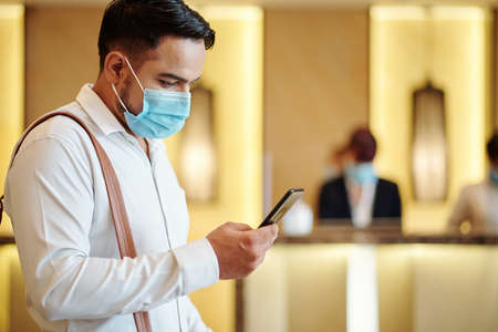 Serious hotel guest in medical mask using mobile application when ordering taxi to airport