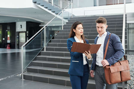 Female entrepreneur showing information in planner to colleague when they are standing in office hall