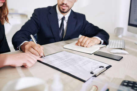 Business lady showing business partner where to sign contract after discussing details of collaboration