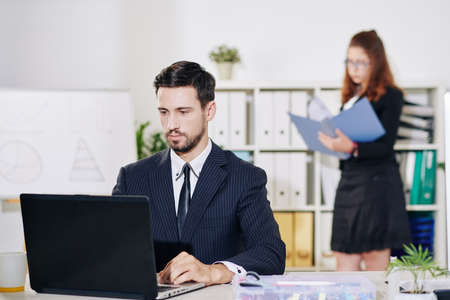 Serious young entrepreneur working on laptop in office his colleague with folder in hands standing in background