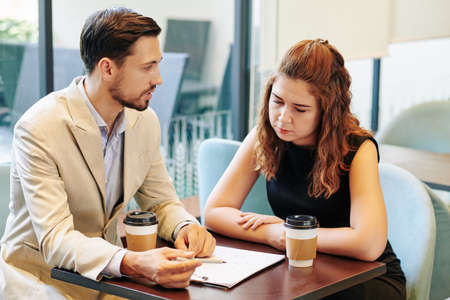 Team of serious young business people drinking take out coffee when discussing chart at meeting