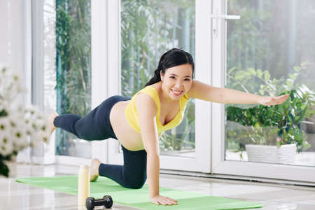 Happy pretty young Vietnamese pregnant woman doing balance exercise on yoga mat
